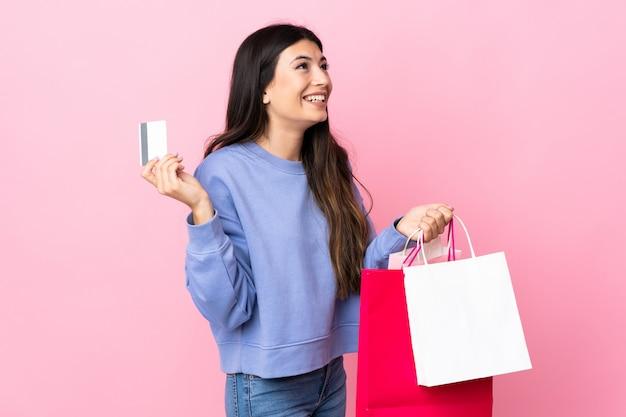 Junges brünettes mädchen über rosa wand, die einkaufstaschen und eine kreditkarte hält