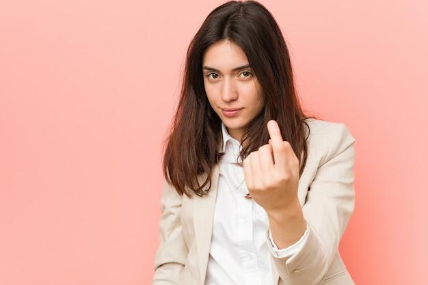 Junges brunettegeschäftsfrau againstpink, das mit dem finger auf sie zeigt, als ob einladung näher kommen.