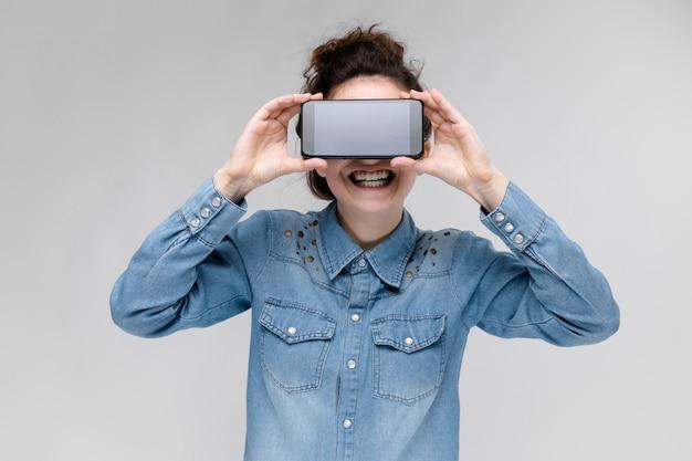 Junges brunettemädchen in den runden gläsern. haare werden in einem brötchen gesammelt. mädchen mit einem schwarzen telefon. das mädchen bedeckte ihr gesicht mit einem telefon.