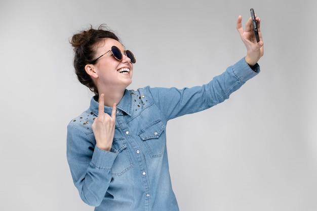 Junges brunettemädchen in den runden gläsern. haare werden in einem brötchen gesammelt. mädchen mit einem schwarzen telefon. das mädchen macht selfie.