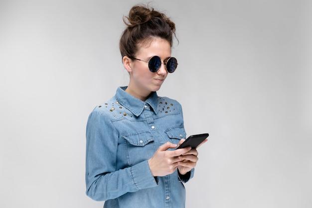Junges brunettemädchen in den runden gläsern. haare werden in einem brötchen gesammelt. mädchen mit einem schwarzen telefon. das mädchen schaut auf das telefon.