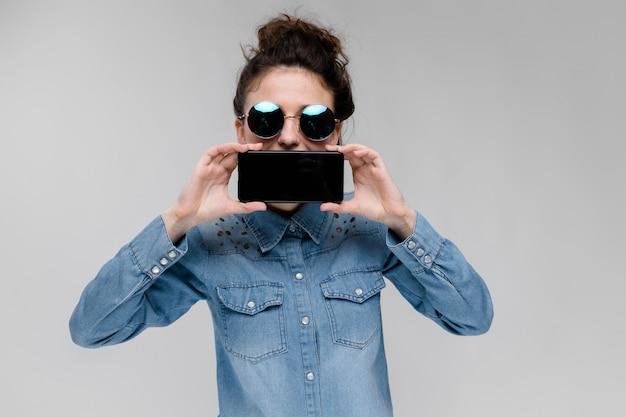 Junges brunettemädchen in den runden gläsern mit einem schwarzen telefon
