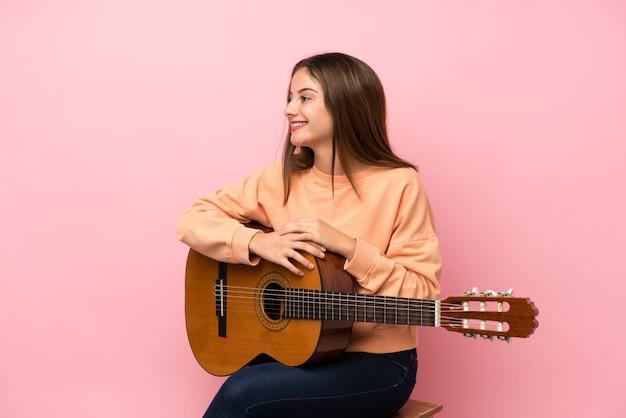 Junges brunettemädchen mit gitarre über getrennter rosafarbener schauender seite