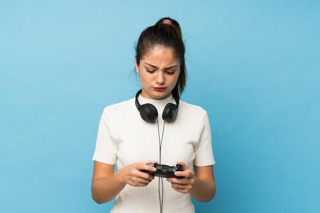 Junges brunettemädchen über dem lokalisierten blau, das an den videospielen spielt