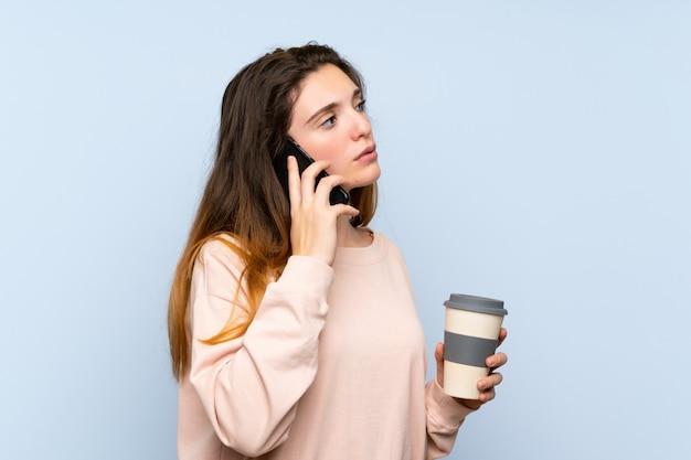 Junges brunettemädchen über der lokalisierten blauen wand, die kaffee hält, um und ein mobile wegzunehmen