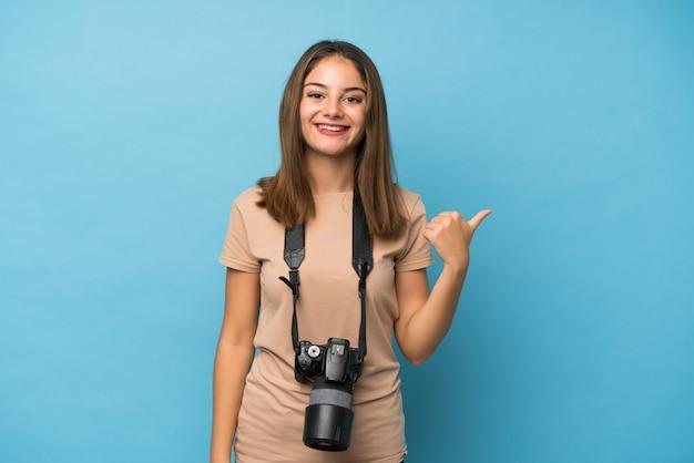 Junges brunettemädchen über getrenntem blau mit einer berufskamera und zeigen auf die seite