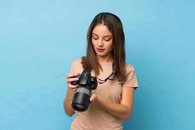 Junges brunettemädchen über getrenntem blau mit einer berufskamera