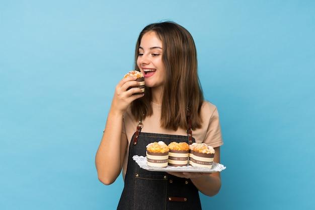 Junges brunettemädchen über lokalisiertem blau, das minikuchen hält und es isst