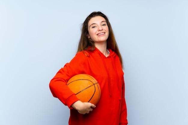 Junges brunettemädchen über lokalisierter blauer wand mit ball des basketballs