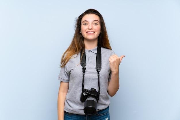 Junges brunettemädchen über lokalisierter blauer wand mit einer berufskamera und zeigen auf die seite