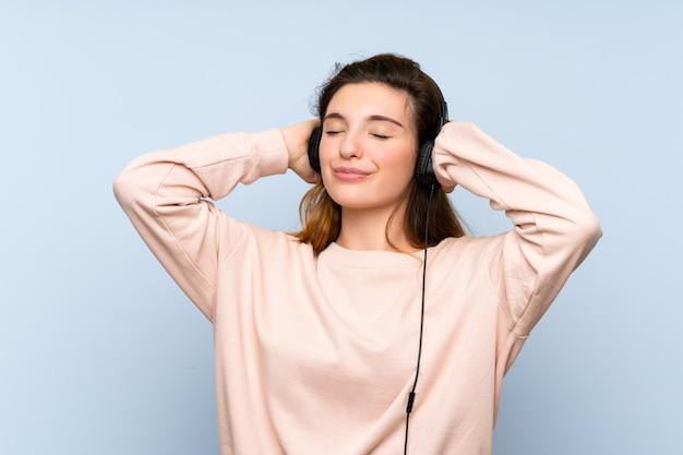 Junges brunettemädchen über lokalisierter blauer wand unter verwendung des mobiles mit kopfhörern