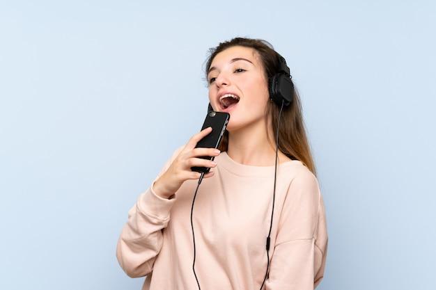Junges brunettemädchen, welches das mobile mit kopfhörern verwendet und singt