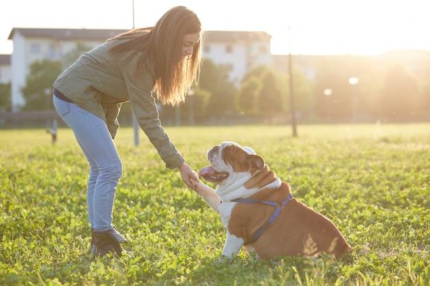 Junges brunettespiel mit ihrer britischen bulldogge