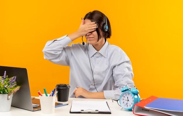 Junges callcenter-mädchen, das headset trägt, sitzt am schreibtisch mit arbeitswerkzeugen, die augen mit hand lokalisiert auf orange hintergrund schließen