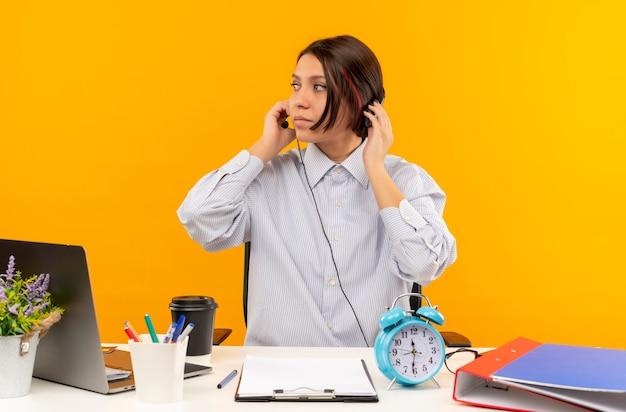 Junges callcenter-mädchen, das headset trägt, sitzt am schreibtisch mit arbeitswerkzeugen, die hände auf headset setzen, das seite lokalisiert auf orangefarbenem hintergrund betrachtet