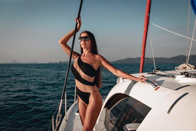 Junges charmantes dunkelhaariges model, das einen schwarzen badeanzug-body mit einem interessanten bikini trägt, der auf ihrer weißen yacht posiert