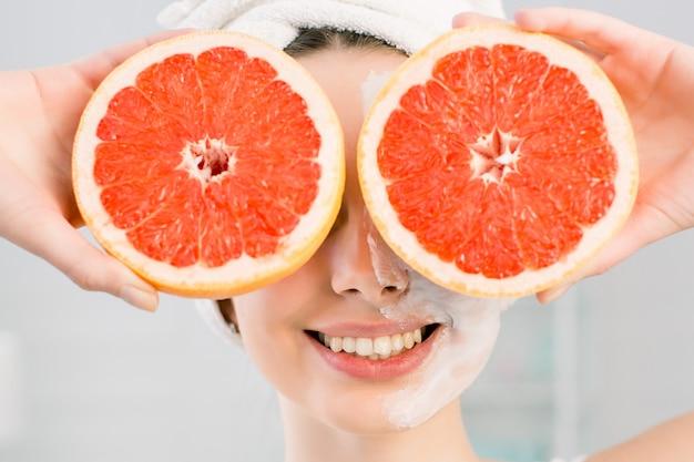 Junges charmantes mädchen, das zwei hälften der grapefruit in den händen hält und ihre augen bedeckt. gesunde ernährung. naturkosmetik, hautpflege, wellness, gesichtsbehandlung, kosmetikkonzept.