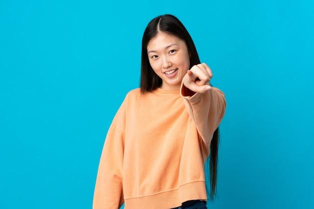 Junges chinesisches mädchen auf isolierter blauer zeigender front mit glücklichem ausdruck