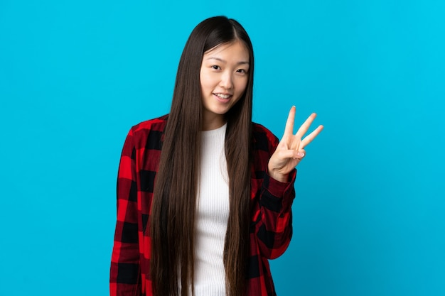 Junges chinesisches mädchen auf lokalem blau glücklich und drei mit den fingern zählend