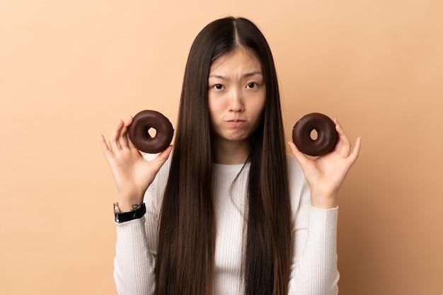 Junges chinesisches mädchen, das donuts mit traurigem ausdruck hält