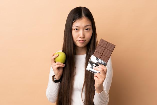 Junges chinesisches mädchen, das eine schokoladentafel in einer hand und einen apfel in der anderen nimmt