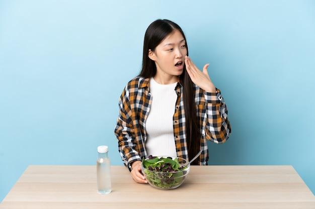 Junges chinesisches mädchen, das einen gähnenden salat isst und weit geöffneten mund mit hand bedeckt
