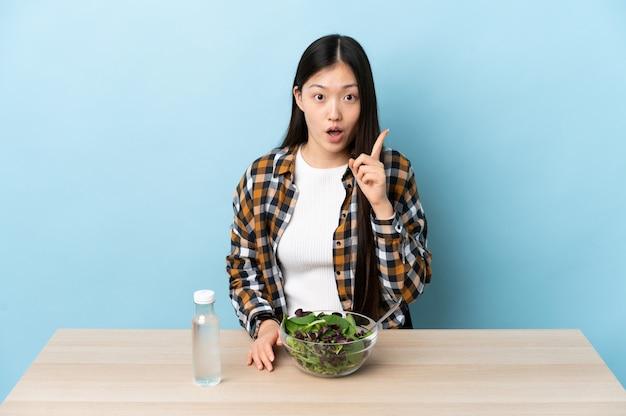 Junges chinesisches mädchen, das einen salat isst, der beabsichtigt, die lösung zu realisieren, während ein finger anhebt