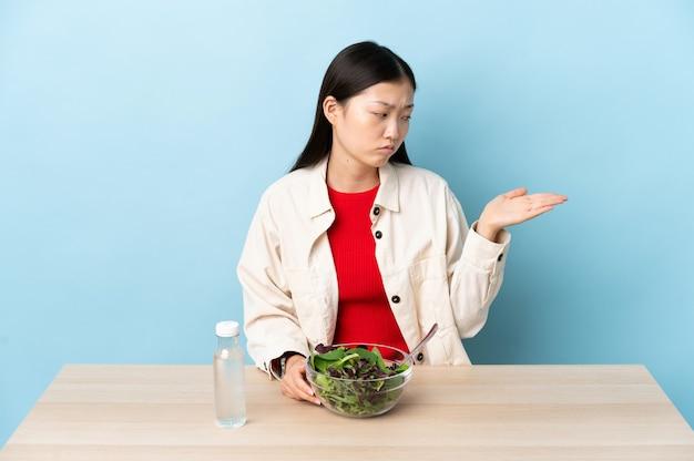 Junges chinesisches mädchen, das einen salat isst, der copyspace mit zweifeln hält