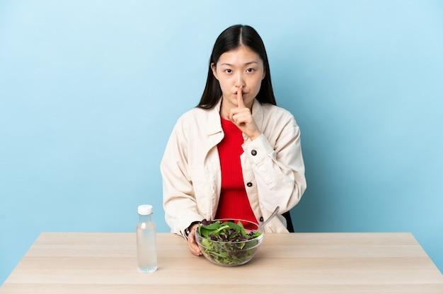 Junges chinesisches mädchen, das einen salat isst, der ein zeichen der stille geste zeigt, die finger in den mund setzt