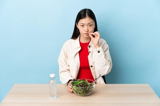 Junges chinesisches mädchen, das einen salat isst, der ein zeichen der stille geste zeigt