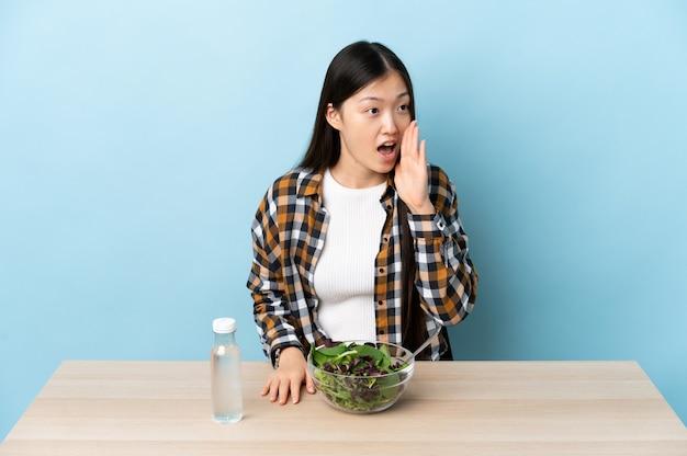 Junges chinesisches mädchen, das einen salat isst, der mit dem mund weit offen zur seite schreit