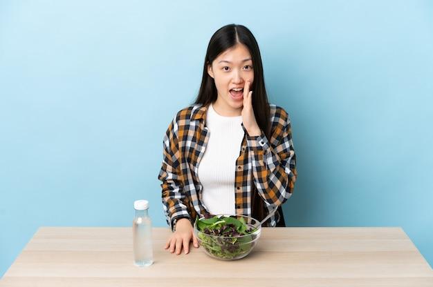 Junges chinesisches mädchen, das einen salat isst, der mit offenem mund schreit