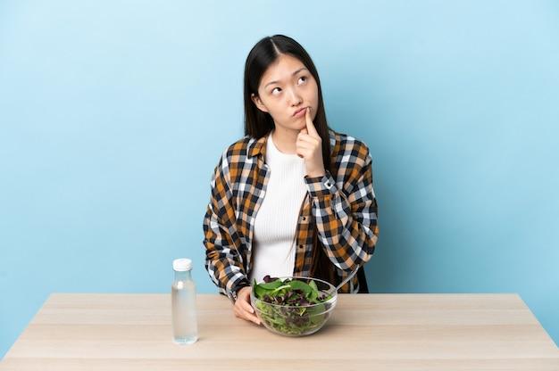 Junges chinesisches mädchen, das einen salat isst, der zweifel beim aufschauen hat