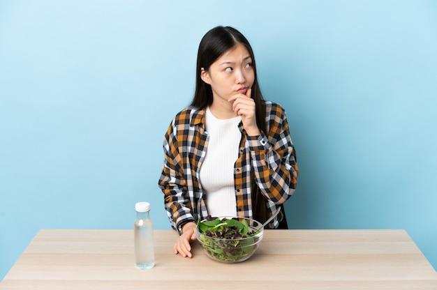 Junges chinesisches mädchen, das einen salat isst, der zweifel und mit verwirrendem gesichtsausdruck hat