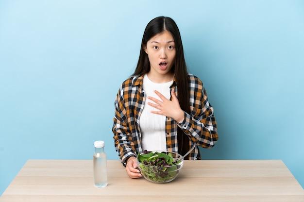Junges chinesisches mädchen, das einen salat isst, überrascht und schockiert, während es richtig schaut