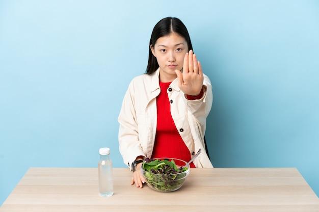Junges chinesisches mädchen, das einen salat macht, der stoppgeste macht