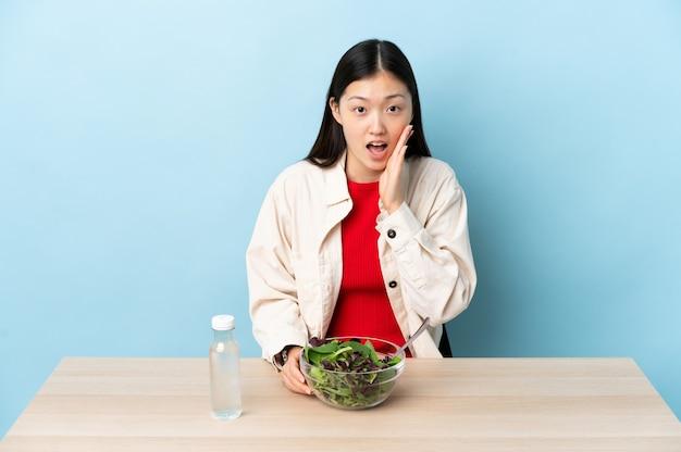 Junges chinesisches mädchen, das einen salat mit überraschung und schockiertem gesichtsausdruck isst