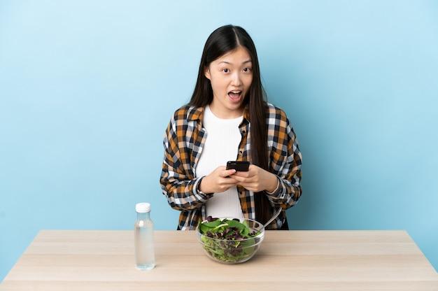 Junges chinesisches mädchen, das einen überraschten salat isst und eine nachricht sendet
