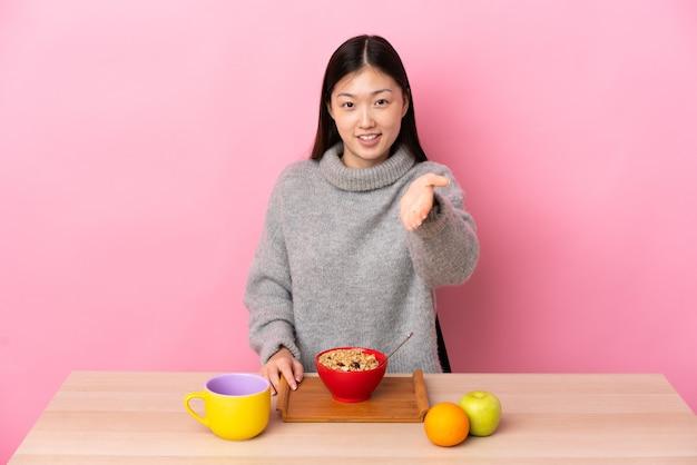 Junges chinesisches mädchen, das frühstück in einem tisch händeschütteln für das schließen eines guten geschäfts hat