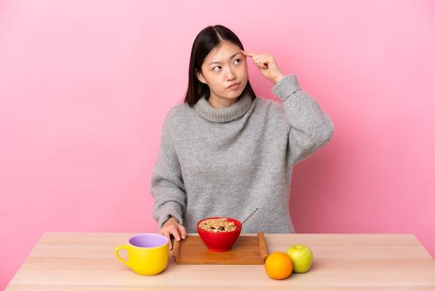 Junges chinesisches mädchen, das frühstück in einem tisch macht, der die geste des wahnsinns macht, der finger auf den kopf setzt
