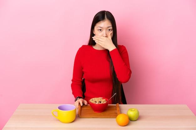 Junges chinesisches mädchen, das frühstück in einer tabelle bedeckt mund mit hand bedeckt
