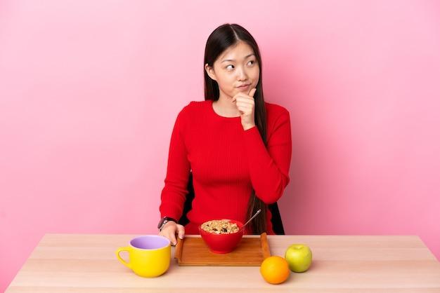 Junges chinesisches mädchen, das frühstück in einer tabelle denkt eine idee beim aufschauen