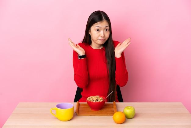 Junges chinesisches mädchen, das frühstück in einer tabelle macht, die zweifel gestikuliert