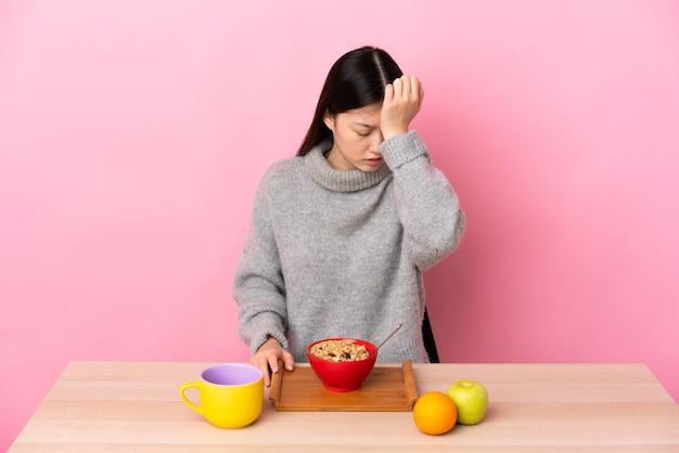 Junges chinesisches mädchen, das frühstück in einer tabelle mit kopfschmerzen hat