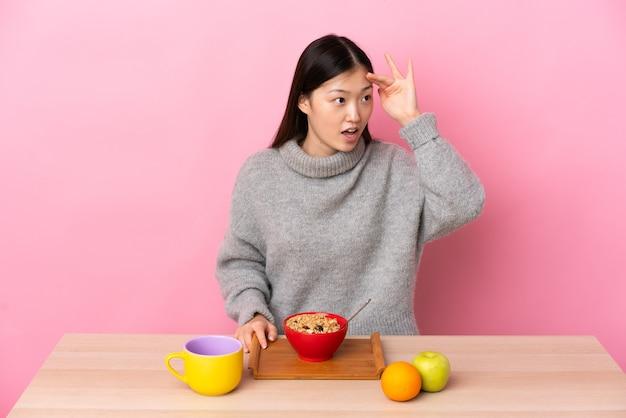 Junges chinesisches mädchen, das frühstück in einer tabelle mit überraschungsausdruck beim betrachten der seite hat