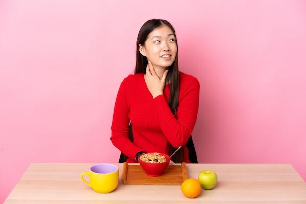 Junges chinesisches mädchen, das frühstück in einer tabelle schaut, während sie lächelt