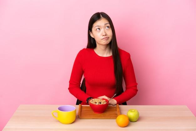 Junges chinesisches mädchen, das frühstück in einer tabelle und nach oben schaut