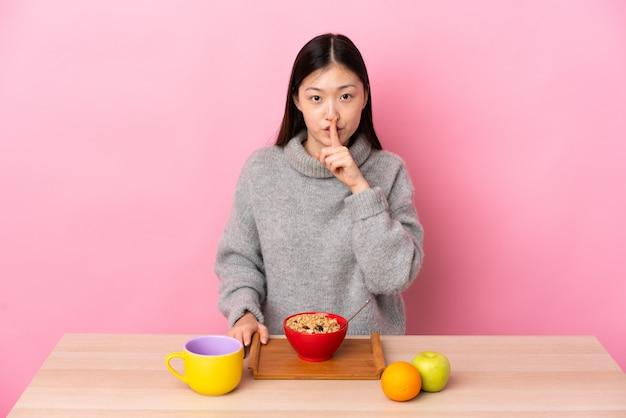 Junges chinesisches mädchen, das frühstück in einer tabelle zeigt, die ein zeichen der stille geste zeigt finger in mund