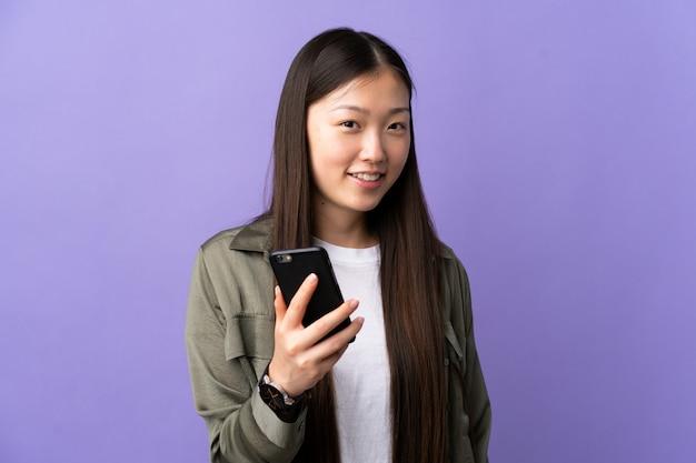 Junges chinesisches mädchen, das handy über isoliertem purpur mit glücklichem ausdruck verwendet