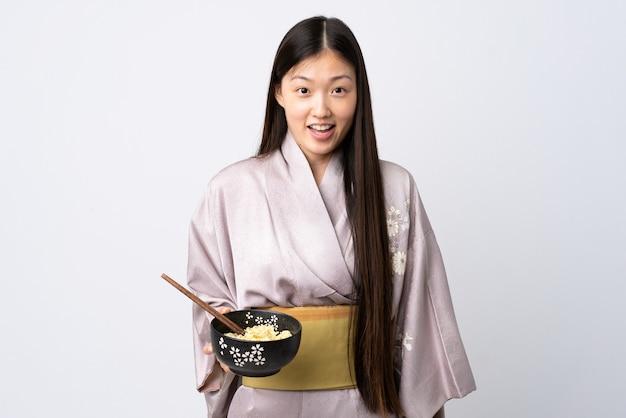 Junges chinesisches mädchen, das kimono auf isoliertem weiß mit überraschung und schockiertem gesichtsausdruck trägt, während eine schüssel nudeln mit stäbchen hält